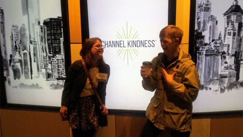 Hanna Joy Atkinson standing with a young man in front of a company logo that reads: Channel Kindness.