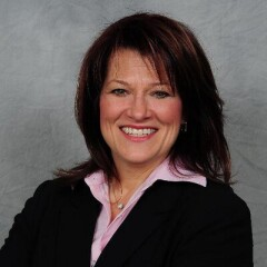 Sharon Bollenbach smiling for a professional photo in a black suite and pink shirt in front of a gray sky background.