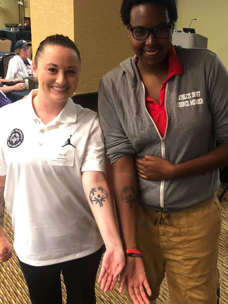 Coach Warner (left) poses for a picture with a member of the Athlete Input Council showing off their support of Special Olympics.