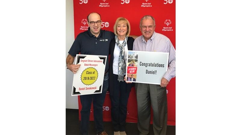 Dan holding a sign that says Class of 2018-2022. He's standing next to a woman and a man. The man is holding a sign that says Congratulations Daniel! They are all standing in front of a Special Olympics 50th Anniversary background.