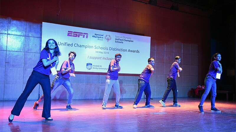 Six young adults on stage putting on a performance. The sign in the background reads Unified Champion Schools Distinction Awards.