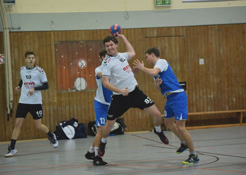 Player prepares to throw the ball while two players from the opposing team attempt to block.