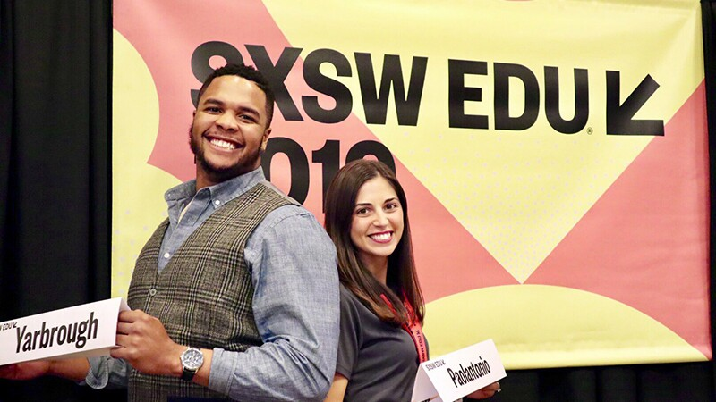 Eddie Yarbrough and teacher Jennifer Paolantonio posing back to back holding their name signs in front of signage for SXSW EDU 2019.