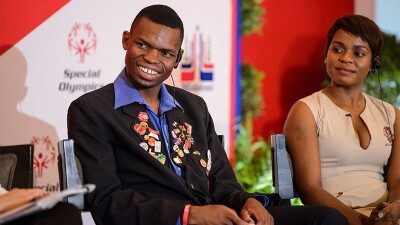Nyasha Derere from Zimbabwe speaks on stage as a panelist during the Global Athlete Congress in Santo Domingo, Dominican Republic. He has on a blue collard shirt with a black jacket that is adorned with Special Olympics and iInclusion pins. A representative is sitting to his left.