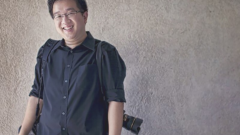 Nicholas Leong standing in front of a cement wall with a camera over either shoulder.