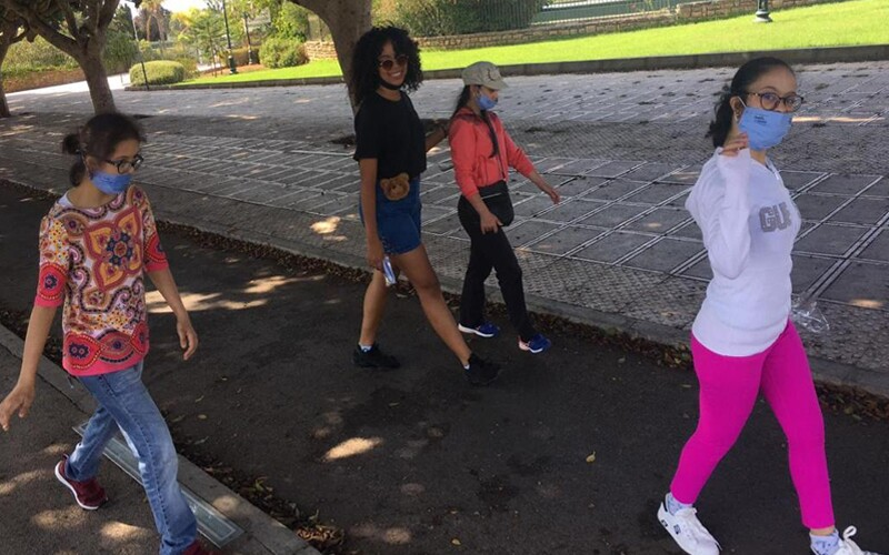 Three young women with masks on and an adult woman walk through a park. One of the youth looks at the camera and waves, and the adult woman has her arm around one of the youth.