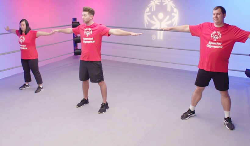 Two athletes and a trainer in the ring performing stretching exercises.