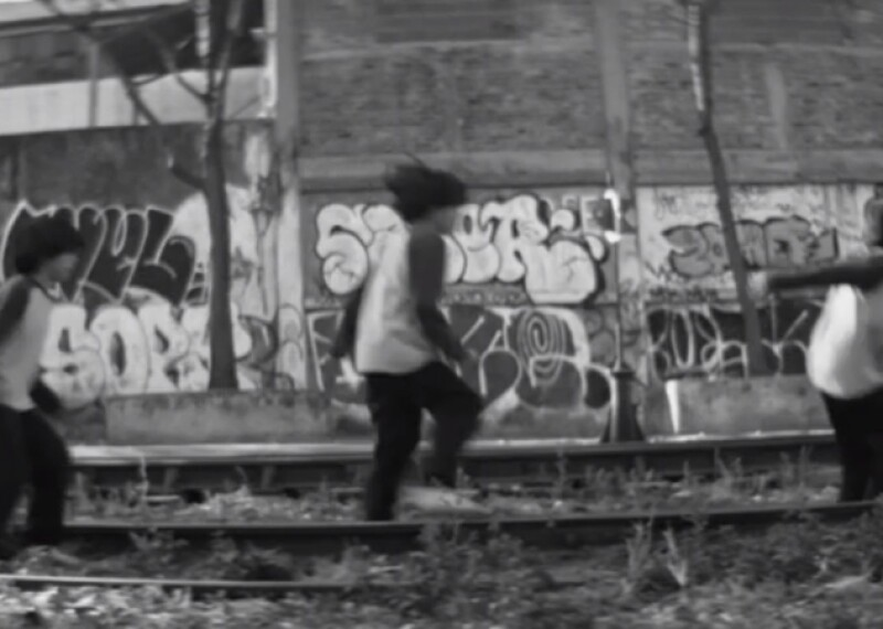 Young boy jumping on rail road tracks in front of a wall that is tagged with graffiti.