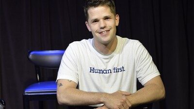 Max Carver sitting and smiling wearing a t-shirt that reads, Human first.