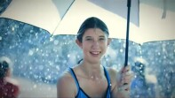 Young woman holding and standing under an umbrella while it's raining.