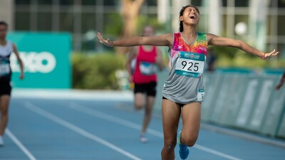 Running athlete crossing the finish line with arm stretched out and celebratory expression on her face.