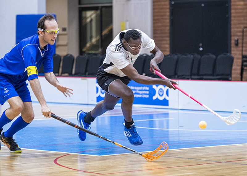 Two athletes from opposing teams playing floorball.