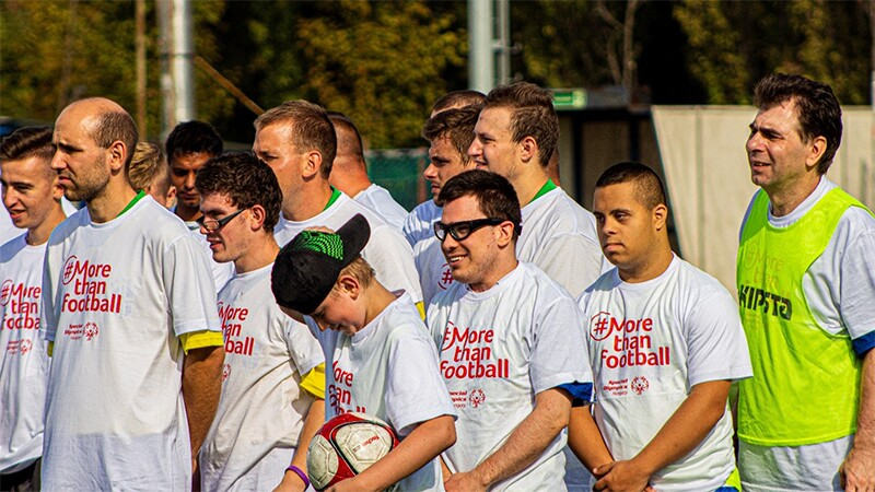 A group of men and boys in white t-shirts with the term #Morethanfootball across the front face off camera.