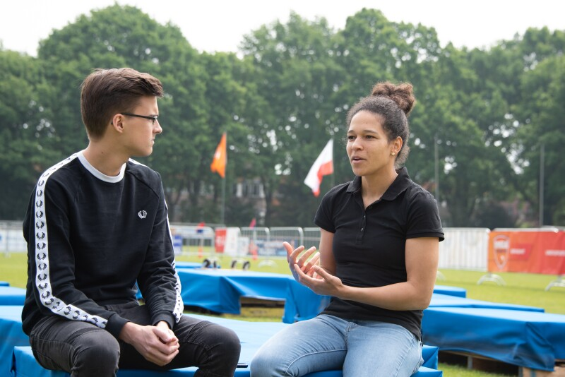 A man and women sit at the side of a football pitch in conversation. Special Olympics flag and hoarding in the background.