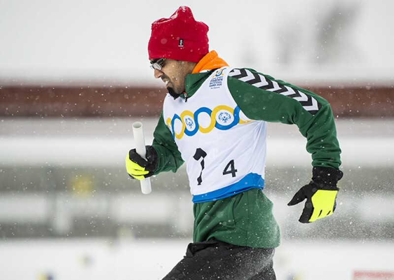 Niklas Claesson of Sweden holds a baton and runs in the snow while snowshoeing.