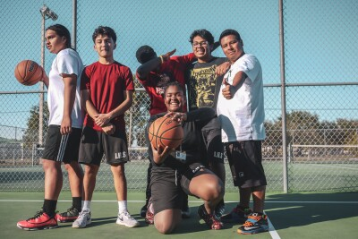 Six diverse students pose on a basketball court