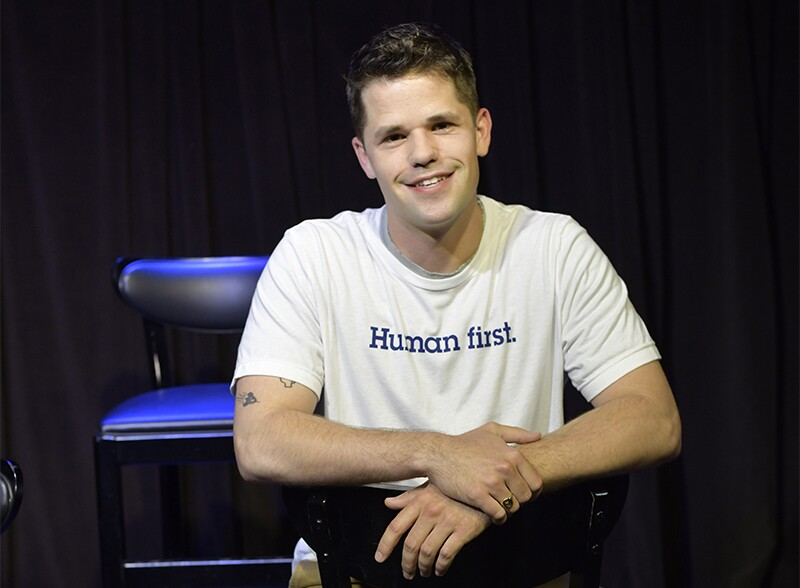 "Max Carer sitting and smiling and wearing a white t-shirt that reads, ""Human first."""