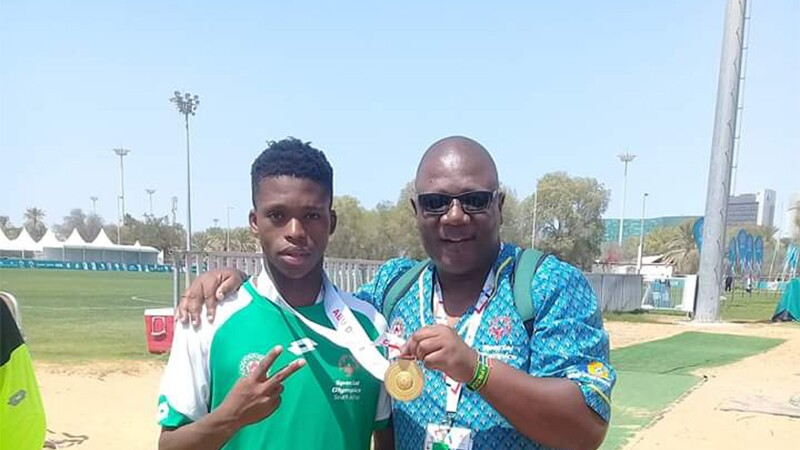 Moeti Clement Sethunya standing with a young male football player.