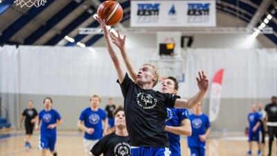 One player jumps for a layup shot; another player attempts to block the shot.
