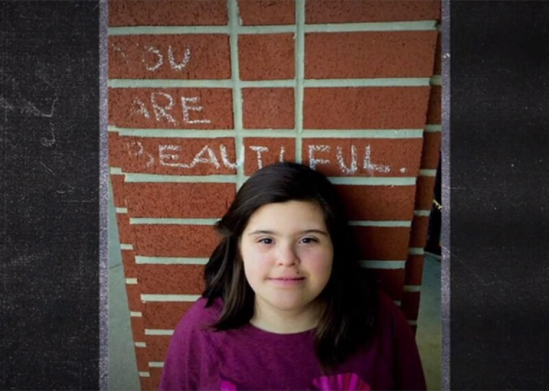 Rosa standing in front of a brick pillar with the word You are Beautiful written above her. She is looking up and smiling for the photo.