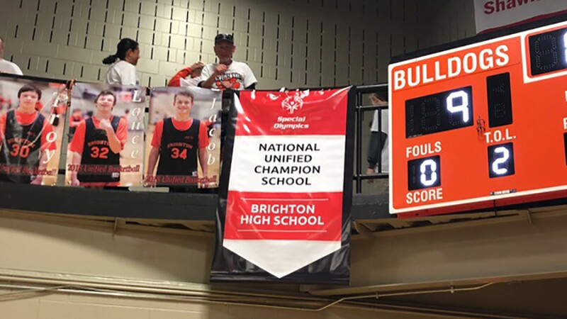 Athlete student photos hanging from a banner along the balcony of a school gym next to a unified champion school banner.