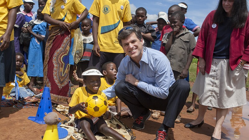 Dr. Timothy Shriver posing outside with a few young athletes and adults.