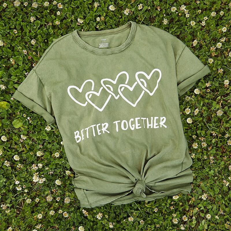 "Aerie ""Better Together"" green t-shirt on a bed of dandelions."