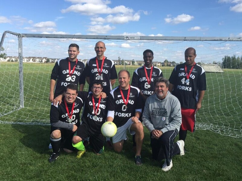 A Special Olympics soccer team smiles at the camera.