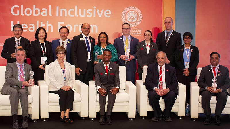 Golisano Global Health Leadership Awards recipients seated on stage: Ms. Ann Costello, Executive Director, Golisano Foundation and Nyasha Derera and Ibtihaj Muhammad both Sargent Shriver International Global Messenger at the Global Health Forum.↵↵Recipients include: Professor Kamal Bani-Hani of Jordan, Dr. Luc Marks of Belgium, Ying Feng from Hua Dong Hospital in China, Dr. Ashok Dhoble of India, Dr. Manoj Shah from The Lions Sight First Eye Hospital in Kenya, Marco Villasboa, Chairmen of the board of Special Olympics Paraguay, is accepting the award on Dr. Ferreira's behalf, Dr. Peter Seidenberg from the United States of America.