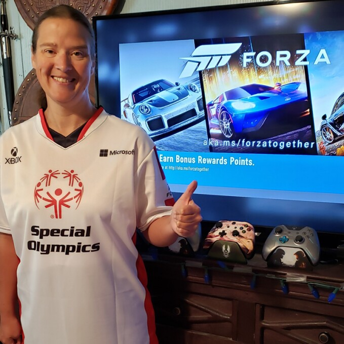 800x800 - Amber Gertsch giving a thumbs up in front of a television screen featuring the game Forza.