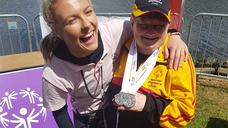 An athlete showing off his two silver medals and a Special Olympics representative are smiling and posing for a photo with their arms around one another's shoulders.