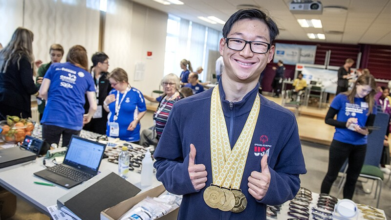 Jay Choi showing off his medals hanging around his neck and giving a double thumbs-up.