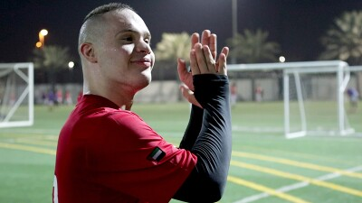 Hamad on he field clapping watching something off in the distance and smiling. He has on a red jersey and a black long sleep undershirt.