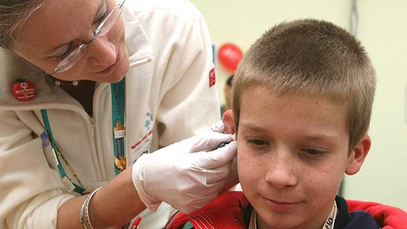 young boy receiving an ear exam from a health care professional.