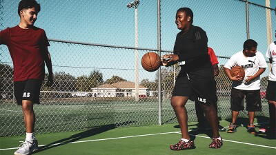 Tajha dribbling the basketball on a court. Other athletes are behind and in front of her.