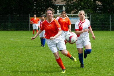 Women in football/soccer jerseys run after a football on a green pitch.