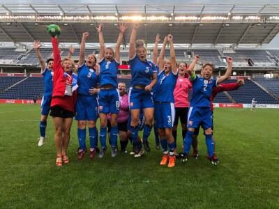 A team of female footballers in a blue kit jump in the air on a football pitch.