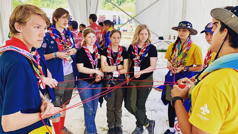 A group of 8 young scouts holding a red string—that each person is holding—to represent inclusion.