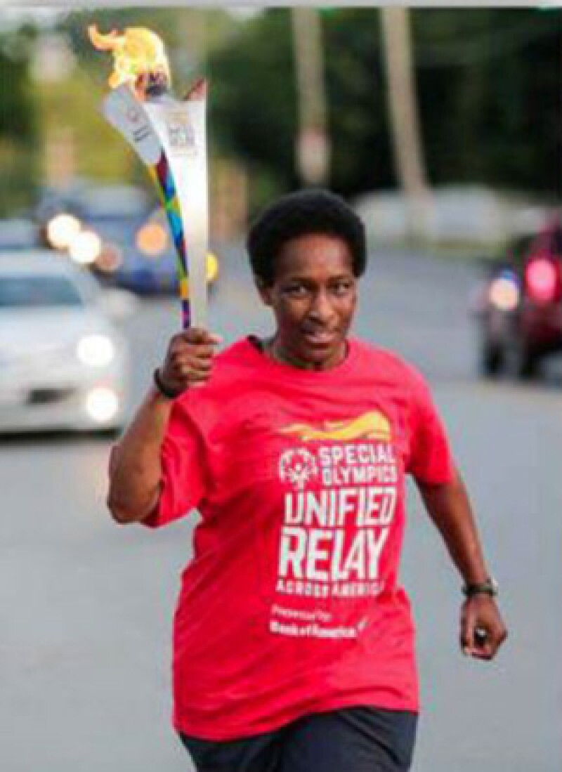 Loretta Claiborne running and carrying the Flame of Hope.