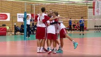 Volleyball team sharing a group hug on the court.