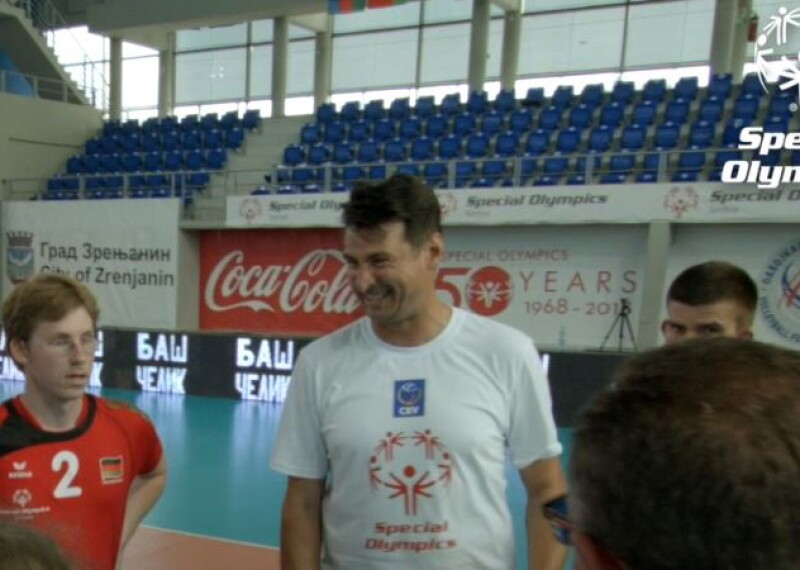 "Vladimir ""Vanja"" Grbic in a huddle with athletes holding a volleyball."