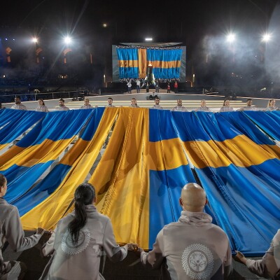 A group of volunteers holding Sweden's flag on stage during the closing ceremony.
