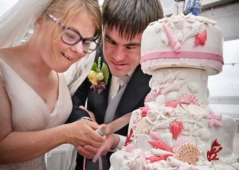 Two Special Olympics Athletes at their wedding cutting cake