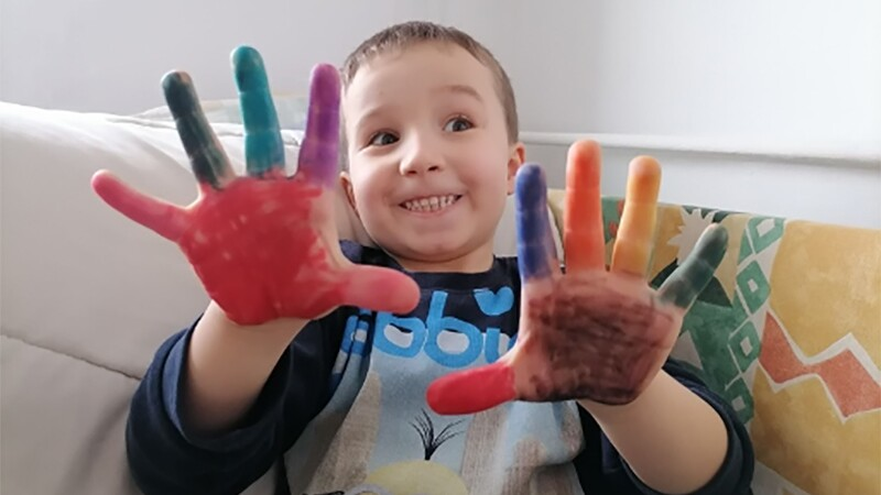 A young boy smiles, looking away, holding his two rainbow-painted hands up to the camera. He sits inside on a couch.