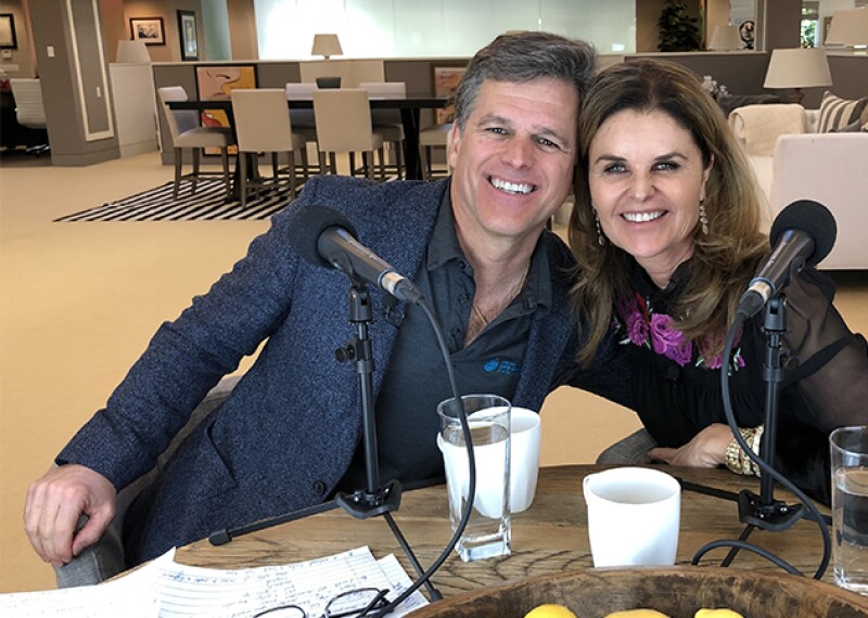 Tim & Maria Shriver sitting next to one another at a table with two mics in front of them.