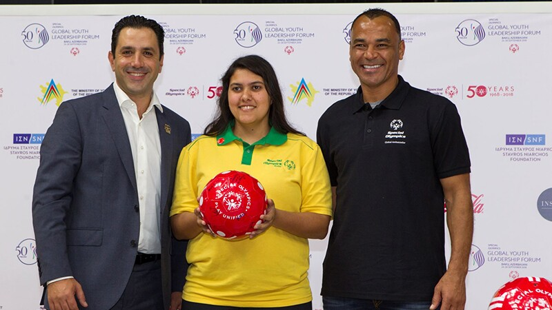 Three people standing side by side facing the camera. A man in a suit, a women holding a read ball and a man in a black Special Olympics t-shirt.