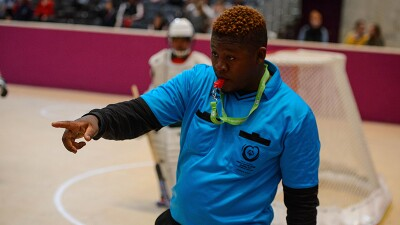 Jimmy blows a red whistle while officiating a floor hockey game at the 2017 World Winter Games in Austria.