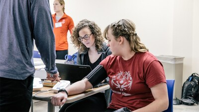 Athlete receiving a blood pressure test while two others stand/sit beside her.