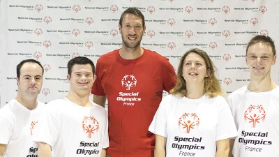 Alain Bernard stands smiling at the centre of the photo wearing a red Special Olympics t-shirt. He is surrounded by four Special Olympics France athletes in white Special Olympics t-shirts,a also smiling.