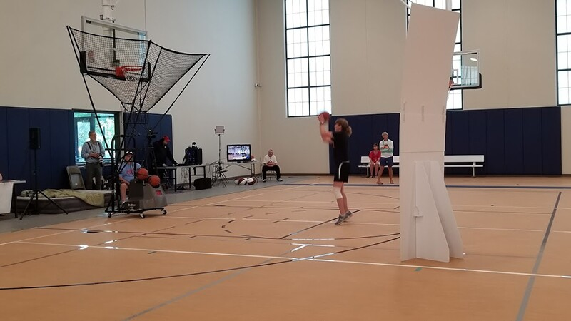 Woman throwing basketball into a basket as spectators and refs watch.